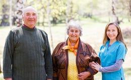 Pares idosos e cuidador novo fotografia de stock royalty free