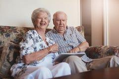 Pares idosos felizes com tabuleta digital em casa imagens de stock
