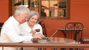 Pares idosos felizes que sentam-se com um portátil filme