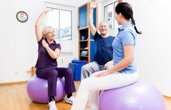 Pares idosos na fisioterapia em bolas ginásticas imagens de stock royalty free
