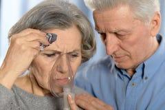 Pares idosos que fazem a inalação Fotografia de Stock