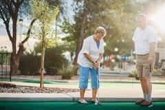 Pares idosos que jogam o mini tiro de golfe com alargamento da lente fotografia de stock royalty free
