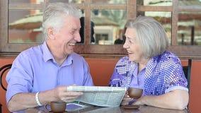 Pares idosos que sentam-se em uma tabela video estoque