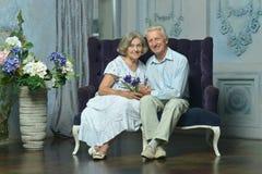 Pares idosos que sentam-se no interior do vintage Fotografia de Stock Royalty Free