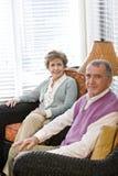 Pares idosos que sentam-se no sofá da sala de visitas Imagem de Stock Royalty Free