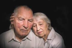 Pares idosos tristes em um fundo preto Fotografia de Stock Royalty Free