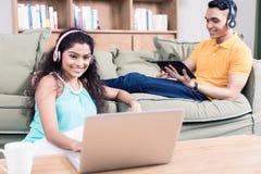 Pares indianos em sua sala de visitas usando o computador imagem de stock