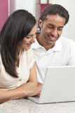 Pares indios asiáticos del hombre y de la mujer usando la computadora portátil fotografía de archivo libre de regalías