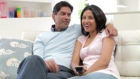 Pares indios que se sientan en Sofa Watching TV junto almacen de metraje de vídeo