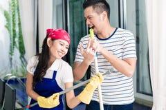 Pares indonésios que têm o divertimento que limpa a casa Fotografia de Stock Royalty Free