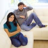 Pares infelices que se sientan en el sofá enojado después de cuadrado de la lucha fotografía de archivo