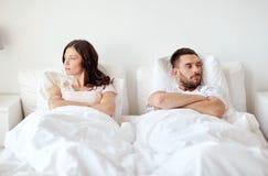 Pares infelices que tienen conflicto en cama en casa fotos de archivo