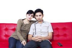 Pares infelizes que olham a tevê e que sentam-se no sofá vermelho Imagem de Stock
