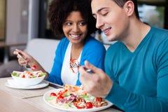 Pares inter-raciais bonitos que têm o almoço Fotografia de Stock