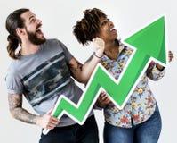 Pares inter-raciais de sorriso felizes que guardam uma seta do crescimento fotos de stock royalty free
