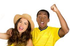 Pares inter-raciais encantadores que vestem as camisas amarelas do futebol que cheering alegremente à câmera, fundo branco do est Fotos de Stock Royalty Free
