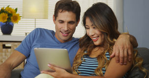 Pares inter-raciais felizes usando a tabuleta junto no sofá Fotos de Stock Royalty Free