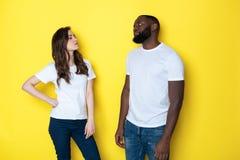 Pares inter-raciais infelizes nos t-shirt brancos que levantam para a câmera no estúdio imagens de stock