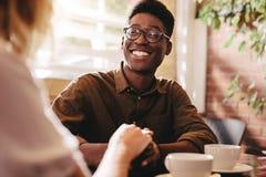Pares inter-raciais na data no café foto de stock