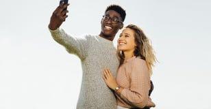 Pares inter-raciais no feriado que toma o selfie fotografia de stock