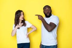 Pares inter-raciais novos forçados nos t-shirt brancos que levantam para a câmera no estúdio imagens de stock royalty free