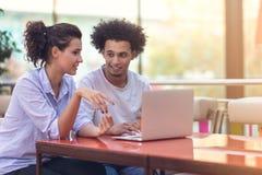 Pares inter-raciais usando o tablet pc na cafetaria imagem de stock