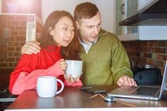 Pares interesantes jovenes que miran un ordenador portátil en casa en la cocina y que sostienen un smartphone Un par internaciona imagen de archivo libre de regalías