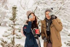 Pares internacionales hermosos que sostienen los copos de nieve y que sonríen en el invierno en la nieve imagenes de archivo