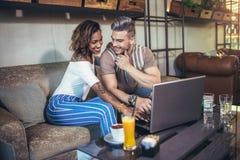 Pares interraciales jovenes que pasan tiempo en café Imagen de archivo