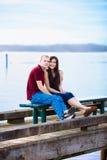 Pares interraciales jovenes que se sientan junto en muelle sobre el lago Foto de archivo libre de regalías