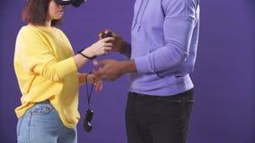 Pares interraciales jovenes que tienen primera experiencia de usar las auriculares de la realidad virtual almacen de video