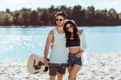 Pares interraciales que abrazan en la playa arenosa mientras que hombre que sostiene la guitarra fotos de archivo libres de regalías