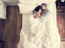 Pares interraciales que duermen junto en la cama fotos de archivo libres de regalías