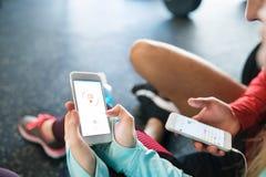 Pares irreconocibles del ajuste en gimnasio con smartphones Imagen de archivo