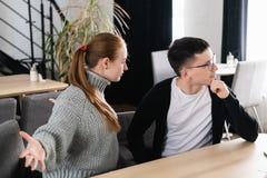 Pares irritados que discutem o assento em um sofá no café O homem ignora sua amiga fotografia de stock royalty free