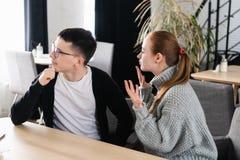 Pares irritados que discutem o assento em um sofá no café O homem ignora sua amiga fotos de stock