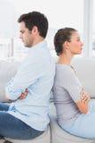 Pares irritados que sentam-se de volta à parte traseira no sofá Fotos de Stock