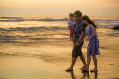Pares japoneses asiáticos felizes e bonitos novos que guardam a filha do bebê que anda na praia do por do sol que aprecia junto r foto de stock royalty free