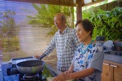 Pares japoneses asiáticos jubilados felices y hermosos mayores que cocinan junto en casa la cocina que goza preparando la comida  fotos de archivo