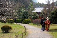 Pares japoneses jovenes tradicionales hacia fuera para un paseo en el parque en Tokio céntrica imagen de archivo