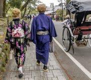 Pares japoneses na roupa tradicional que anda abaixo da rua perto de um riquexó em Kyoto, Japão imagem de stock