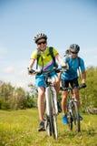Pares jovenes ACTIVOS biking en un camino forestal en montaña en un spr imagenes de archivo