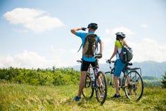 Pares jovenes ACTIVOS biking en un camino forestal en montaña en un spr Imagen de archivo libre de regalías