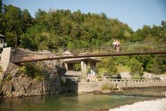 Pares jovenes activos en un puente sobre el río alpino en verano caliente Imagenes de archivo