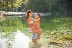 Pares jovenes activos que se enfrían hacia fuera en el río en un día de verano caliente s Foto de archivo libre de regalías