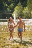 Pares jovenes activos que se enfrían hacia fuera en el río en un día de verano caliente s Fotografía de archivo libre de regalías