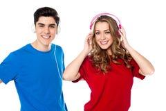 Pares jovenes adorables que disfrutan de música Foto de archivo libre de regalías