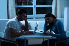 Pares jovenes agujereados usando la tableta y el ordenador portátil digitales Fotos de archivo libres de regalías