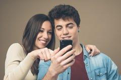 Pares jovenes alegres con el teléfono móvil Imágenes de archivo libres de regalías