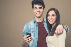 Pares jovenes alegres con el teléfono móvil Fotos de archivo libres de regalías